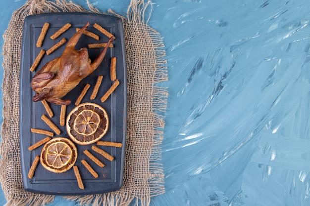 Grill, getrocknete zitrone und croutons auf einem tablett auf der sackleinenserviette, auf blauem hintergrund.