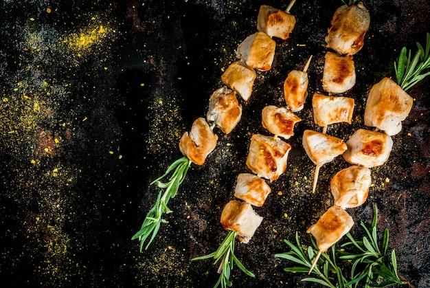 Grill, grillfleisch. hühnerspieße mit rosmarin. auf einer schwarzen rostigen metallischen, draufsicht