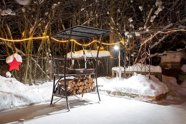 Grill im winter in der nähe des hauses. nacht, girlanden brennen, es schneit. vorbereitung zum braten von fleisch. sie legen geerntetes brennholz unter den grill.