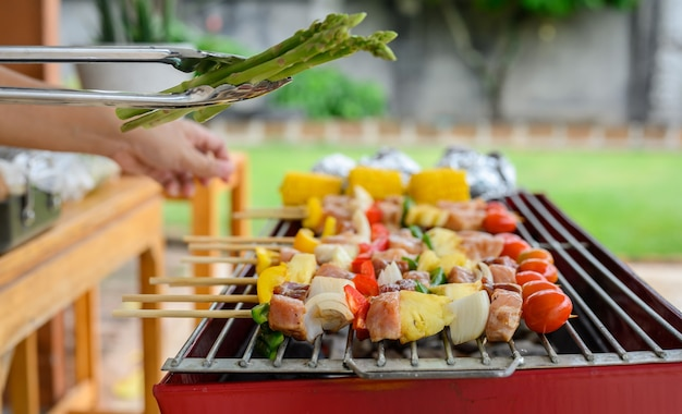 Grill- und grillparty zu hause. kochen von bbq-schweinefleisch, rindfleisch, hühnchen, meeresfrüchten und gemüse. familienlebensstil und outdoor-aktivität für freunde.
