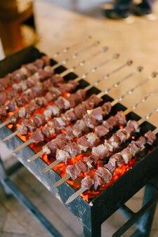 Grillen auf dem grill schaschlik aus fleischwürfeln auf den spießen beim kochen auf dem mangal man