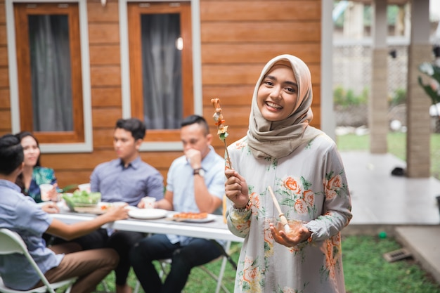 Grillen der muslimischen frau mit freunden
