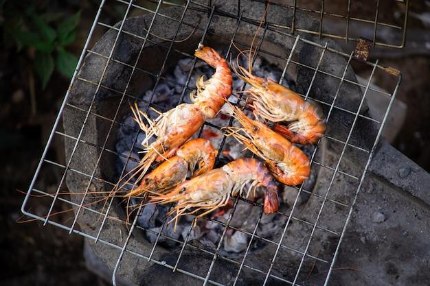 Grillen eines garnelengrills in der thailändischen meeresfrüchteart. traditionelles grillen mit schwarzem holzkohleholz. draufsicht nah oben.