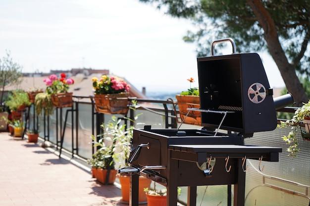 Grillen sie auf der terrasse mit vielen blumen und einer schönen aussicht