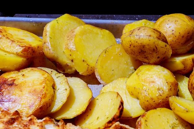 Grillen sie die kartoffeln, die auf gebratenen hauptkartoffeln auf dem grillhintergrund gebraten werden