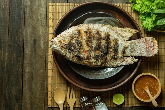 Grillen sie draufsicht des fisch- und meeresfrüchtesoßenkalkes über hölzerne tabelle
