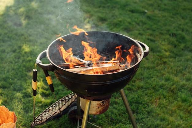 Grillen sie grill mit feuer auf gras am park