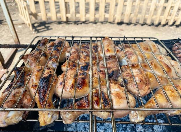 Grillen sie hühnchen und würstchen auf dem grill. ruhe in der natur, grillen.