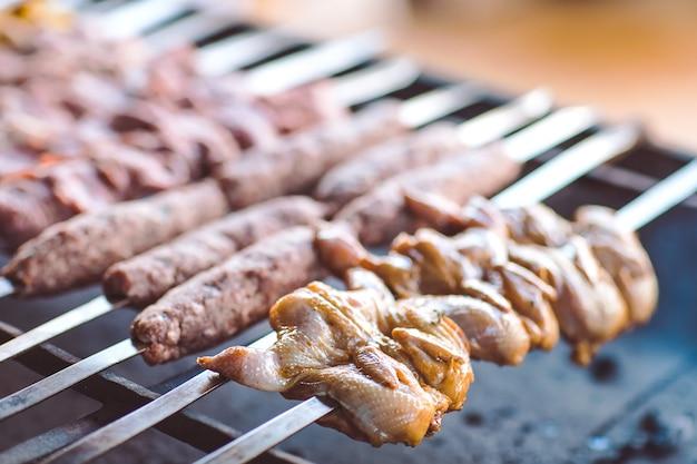 Grillen sie im restaurant vor dem hintergrund der gäste aus verschiedenen fleischsorten.