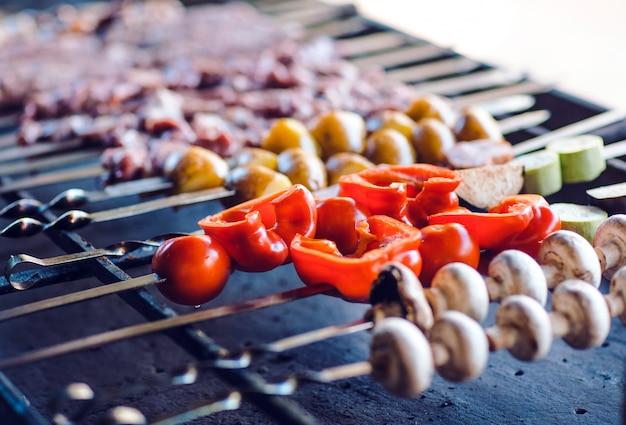 Grillen sie im restaurant vor dem hintergrund der gäste verschiedene fleischsorten.