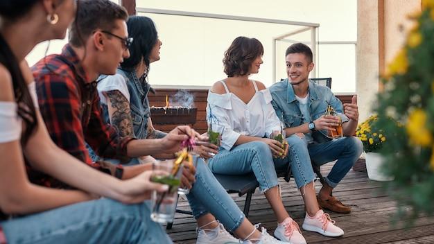 Grillen sie junge, fröhliche leute, die sich unterhalten und cocktails trinken, während sie auf dem dach sitzen