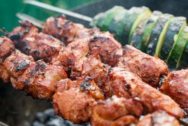 Grillen von fleisch im freien, kebab, grillen, mariniertes gemüse