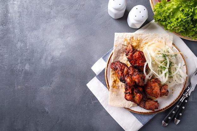 Grillfleisch mit zwiebeln auf einem teller. kebabs, speicherplatz kopieren. draufsicht