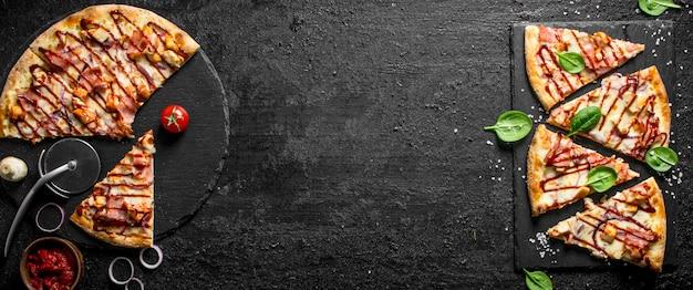 Grillpizza auf einem steinbrett schneiden. auf schwarzem rustikalem hintergrund