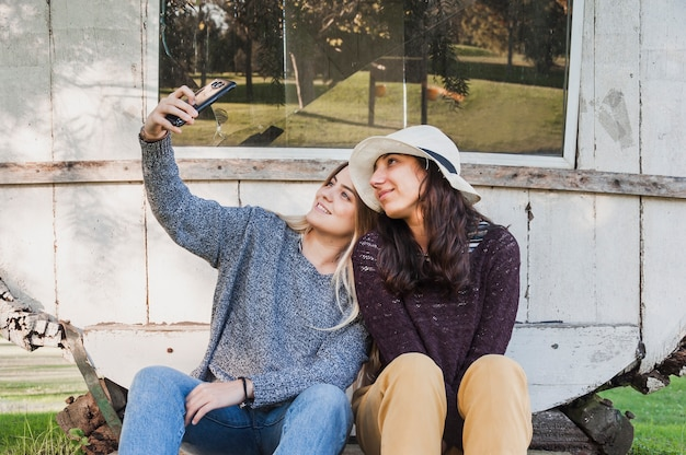 Grills, die im park sitzen und selfie im handy nehmen