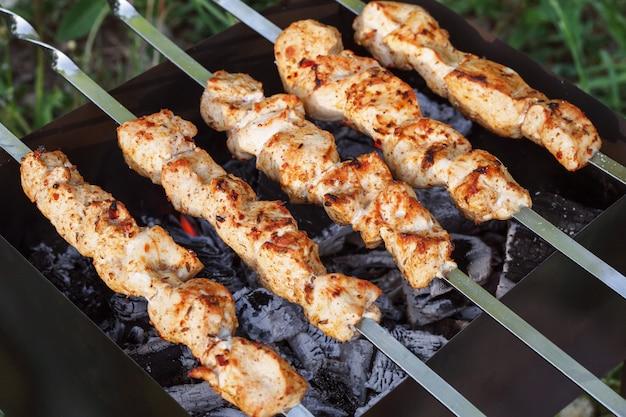 Grillspieße mit fleisch auf dem kohlenbecken. hühnchen-schaschlik