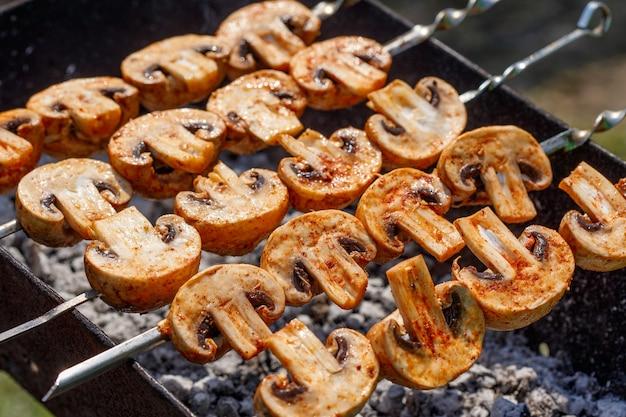 Grillspieße mit leckerem gegrilltem champignon-pilz-kebab in einer kohlenpfanne