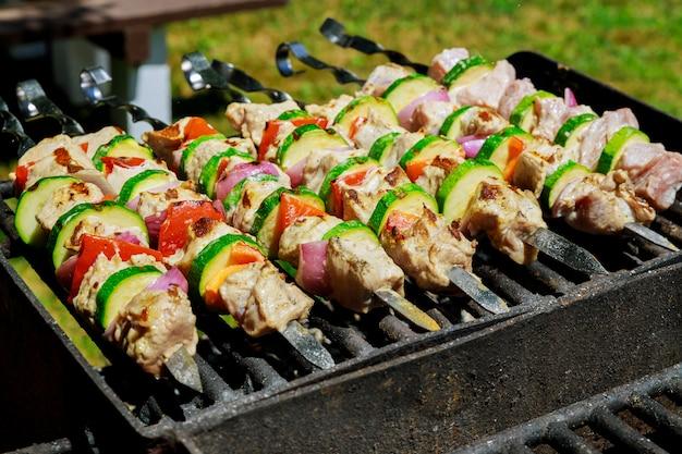 Grillspieße schaschlik mit gemüse auf brennendem grill.