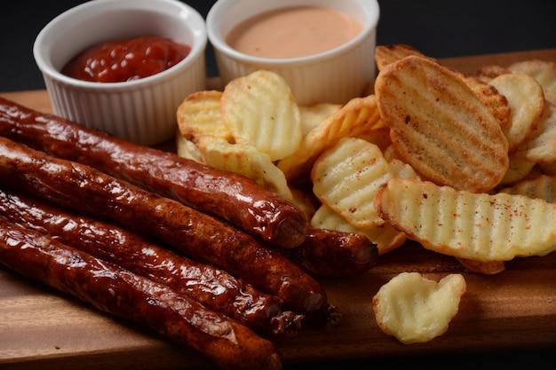 Grillwürstchen mit hausgemachten kartoffelchips und sauce, ketchup