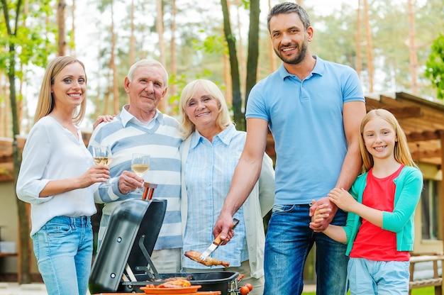 Grillzeit. glückliche fünfköpfige familie, die fleisch auf dem grill grillt und in die kamera schaut