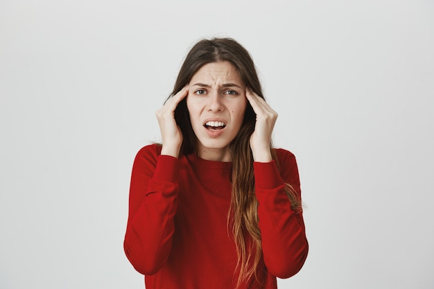 Grimassende frau, die sich über kopfschmerzen oder migräne beschwert