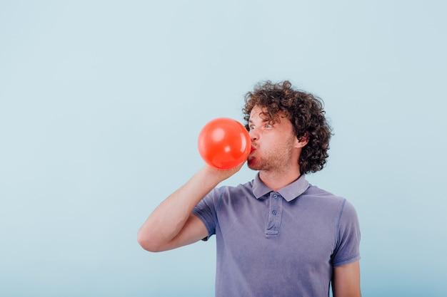 Grimassender unrasierter mann mit lockigem haar im blauen hemd, das roten ballon bläst