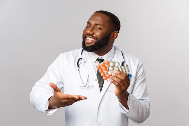 Grippe-, krankheits-, gesundheits- und medizinkonzept. glücklicher afroamerikanischer männlicher arzt im weißen kittel präsentiert neue medikamente, heilung von krankheiten oder viren und zeigt pillen, die eine gute behandlungsqualität garantieren