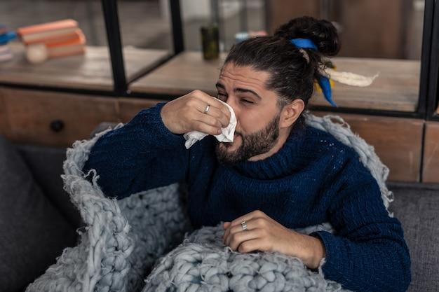 Grippesymptome. unglücklicher junger mann, der an einer laufenden nase leidet, während er grippe hat