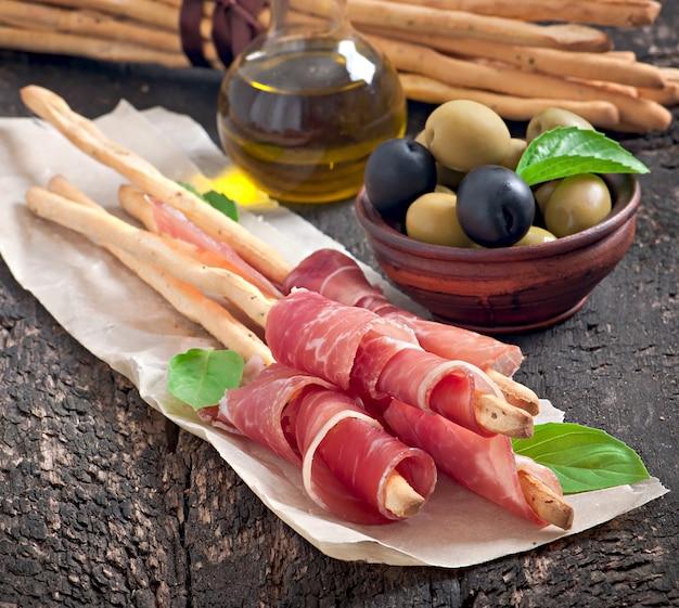 Grissini-brotstangen mit schinken, oliven, basilikum auf altem holz