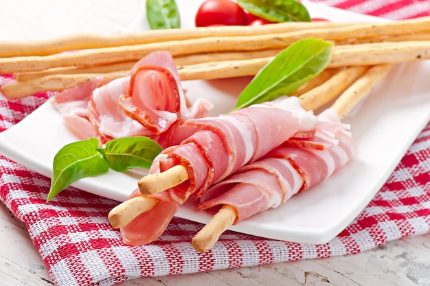 Grissini-stangenbrot mit schinken, tomate und basilikum