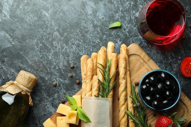 Grissini-sticks, snacks und wein auf schwarzem rauchigem hintergrund