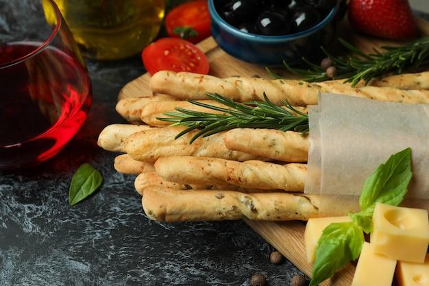 Grissini-sticks, snacks und wein auf schwarzer, rauchiger oberfläche