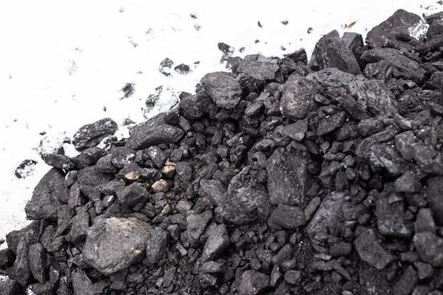 Grobe kohle im schnee im winter. aufrechterhaltung hoher temperaturen in brennstoffkesseln, heizungssystemen für privathaushalte. brennbares mineral.