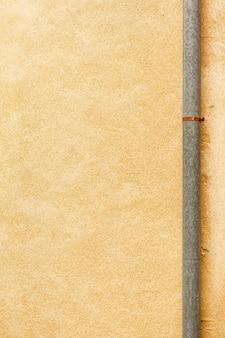 Grobe wandfläche mit rohr und rost