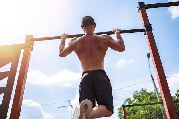 Grober athletischer mann, der klimmzugübungen auf einer querlatte macht.