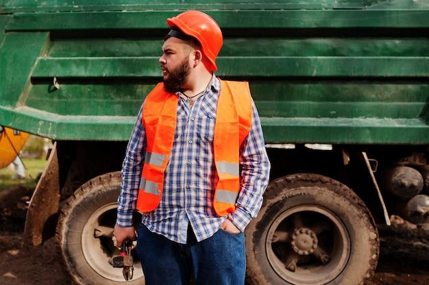 Grober bartarbeitskraftmann-klagenbauarbeiter im orange sturzhelm der sicherheit, gegen kipper mit dem hammer und justierbarem schlüssel zur hand.