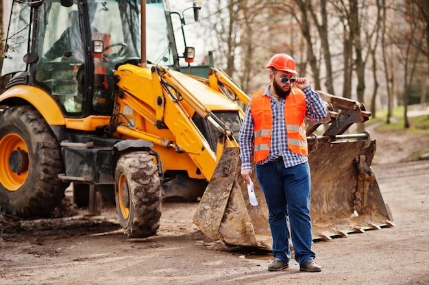 Grober bartarbeitskraftmann-klagenbauarbeiter im orange sturzhelm der sicherheit, sonnenbrille gegen traktor mit planpapier an den händen.