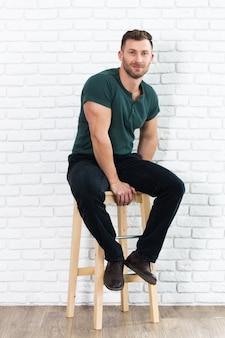 Grober gutaussehender mann, der auf stuhl sitzt