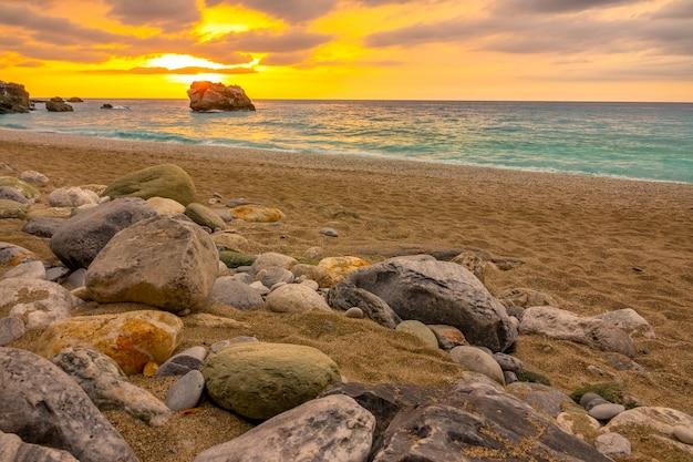 Grober sandstrand mit bunten steinen. goldener sonnenuntergang über dem ruhigen meer