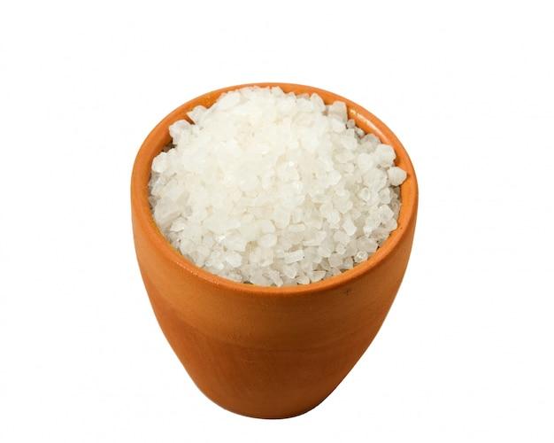 Grobes salz in einer schüssel auf einem weißen hintergrund.
