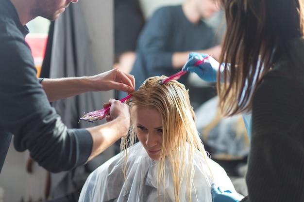 Grodno, weißrussland - 20. oktober 2016: der technologe der marke keune, artem raychuk, färbt die haare eines models im werbeworkshop mit der teilnahme am schönheitssalon kolibri.