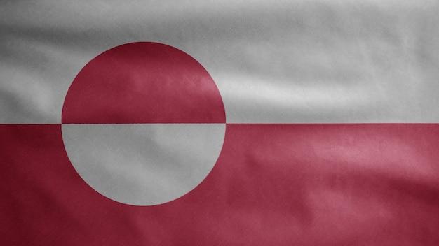 Grönländische flagge weht im wind. nahaufnahme von grönland banner weht, weiche und glatte seide. stoff textur fähnrich hintergrund.