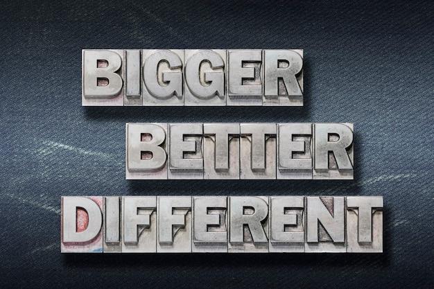 Größere, bessere, verschiedene wörter aus metallischem buchdruck auf dunklem jeanshintergrund