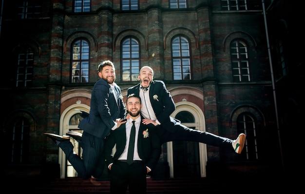 Groomsmen in eleganten anzügen springen auf den rücken des bräutigams