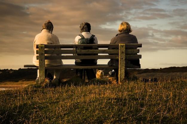 Großartige aussicht auf drei frauen, die auf einer bank sitzen und den blick auf den bristol-kanal bei sonnenuntergang genießen