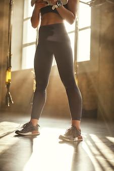 Großartige formnahaufnahme einer jungen athletischen frau mit perfektem körper in sportleggings steht