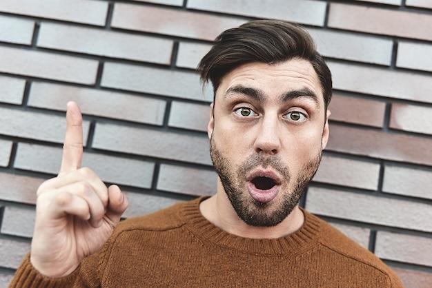 Großartige idee! hübscher mann, der den finger nach oben zeigt, etwas über seinem kopf zeigt und mit dem zeigefinger eine geste macht. eureka, lösungszeichenkonzept.
