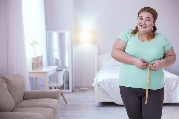 Großartige neuigkeiten. aufgeregte junge frau, die ihre maße bewundert, während sie ein breites lächeln teilt