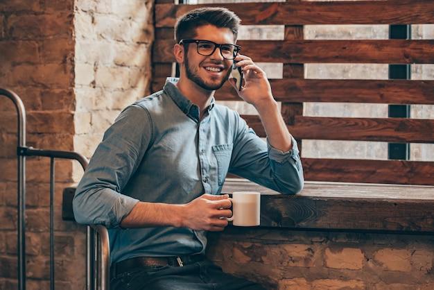Großartige neuigkeiten! hübscher junger mann, der mit dem handy spricht und lächelt, während er in der nähe des fensters im loft-interieur mit einer kaffeetasse in der hand sitzt