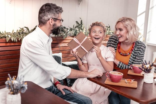 Großartige stimmung. fröhliches aufgeregtes mädchen lächelnd, während sie ihren geburtstag mit familie feiern